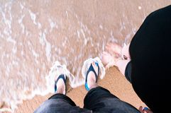 Tiro de mirada hacia abajo de los pares que se colocan en una playa con las ondas c Fotografía de archivo libre de regalías
