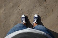 Tiro de Point of View de una mirada del hombre abajo a sus pies que se colocan en la carretera nacional Imagen de archivo