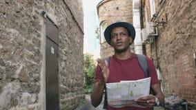Tiro de Steadicam de la ciudad de papel que camina y de observación turística afroamericana del hombre para trazar para encontrar almacen de metraje de vídeo