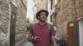 Tiro de Steadicam de la guía que camina y de observación turística feliz del hombre de la ciudad en su smartphone para encontrar  almacen de video