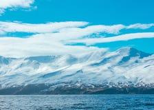 Tiro de surpresa de montanhas nevados e do mar fotos de stock