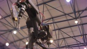 Tiro de trabajar el mecanismo robótico automático negro del laser en proceso en fondo de la exposición almacen de metraje de vídeo
