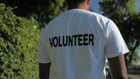 Tiro de Trackig de um voluntário agradável que anda no parque vídeos de arquivo