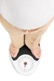 Tiro de um homem que está em uma escala do peso Foto de Stock Royalty Free