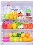 Tiro de um refrigerador aberto com produtos de alimento imagens de stock