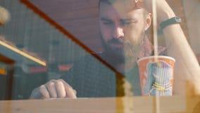 Tiro de un hombre que se sienta en café con un café del smartphone y de la bebida almacen de metraje de vídeo