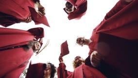 Tiro del ángulo bajo de la cámara lenta de los graduados que se colocan en mortero-tableros que lanzan del círculo en el cielo y  metrajes