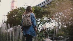 Tiro del ángulo bajo de la muchacha joven del viajero con la mochila que camina bajo cámara lenta de Brooklyn del puente de los á metrajes