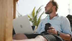 Tiro del ángulo bajo del hombre cómodo feliz acertado del freelancer con el ordenador portátil y de la bebida que descansa en sil metrajes