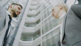 Tiro del ángulo bajo del hombre de negocios barbudo que sacude las manos y que habla con el colega femenino del negocio en traje