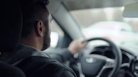 Tiro del asiento trasero de un coche de un hombre que conduce en ciudad metrajes