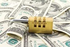 Tiro del candado de la combinación sobre la pila dólar americano Imagen de archivo libre de regalías