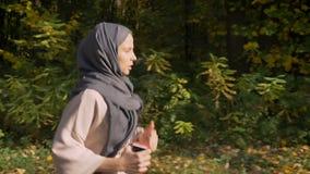 Tiro del carro, de la parte inferior para rematar a la muchacha musulmán en el hijab que corre con el teléfono en bosque otoñal almacen de metraje de vídeo