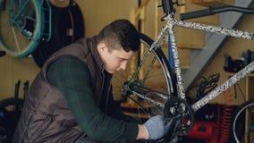 Tiro del carro del reparador joven concentrado que fija el pedal roto de la bici que se sienta cerca de la bicicleta moderna en l almacen de video