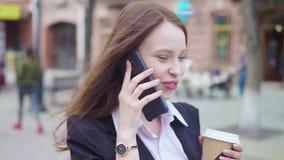 Tiro del carro del smartphone que habla atractivo de la mujer de negocios de la raza mixta y de los paseos de consumición del caf almacen de video