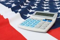 Tiro del estudio de la bandera nacional rizada con la calculadora sobre ella - los Estados Unidos de América Fotografía de archivo