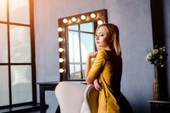 Tiro del estudio de la muchacha joven y hermosa que se coloca en el vestido de cuero amarillo que lleva en estudio Muchacha rubia Imágenes de archivo libres de regalías