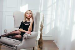Tiro del estudio de la muchacha joven y hermosa que se sienta en el vestido negro que lleva en estudio Muchacha rubia Foto de archivo libre de regalías