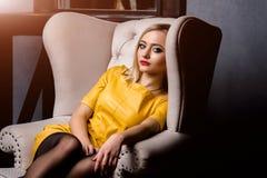 Tiro del estudio de la muchacha joven y hermosa que se sienta en silla en el vestido de cuero amarillo que lleva en estudio Mucha Foto de archivo libre de regalías
