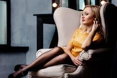 Tiro del estudio de la muchacha joven y hermosa que se sienta en silla en el vestido de cuero amarillo que lleva en estudio Mucha Imagen de archivo libre de regalías