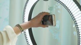 Tiro del estudio de la mujer joven y hermosa que toma la imagen del selfie con el teléfono móvil delante de la lámpara del anillo metrajes