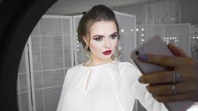 Tiro del estudio de la mujer joven y hermosa que toma la imagen del selfie con el teléfono móvil delante de la lámpara del anillo almacen de video