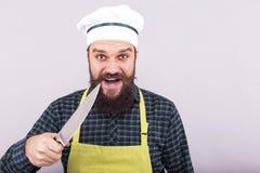 Tiro del estudio de un hombre joven barbudo con holdi del sombrero del delantal y del cocinero foto de archivo libre de regalías