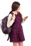 Tiro del estudio del estudiante sonriente con la mochila que mira su sma Fotografía de archivo