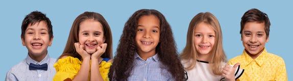 Tiro del estudio del grupo Multi-étnico de schoolchilds sonrientes, aislado en fondo azul imagenes de archivo