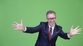 Tiro del estudio del hombre de negocios maduro feliz con gesto de la sorpresa almacen de metraje de vídeo