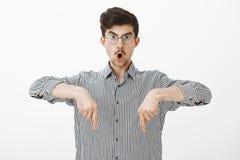 Tiro del estudio del individuo joven creativo sorprendente chocado con el bigote en vidrios, señalando abajo con los dedos índice Foto de archivo