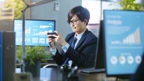 Tiro del hombre de negocios asiático del este Plaing Video Games en su SM imagen de archivo libre de regalías