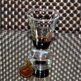 Tiro del licor de café Kahlua con un descenso del alcohol en el espejo Foto de archivo