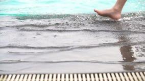 Tiro del movimento lento dei piedi che camminano dallo stagno Piccolo bambino che cammina vicino alla piscina stock footage