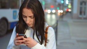 Tiro del PDA de la mujer joven que manda un SMS en el teléfono móvil en la calle de la noche delante del fondo borroso con los co metrajes