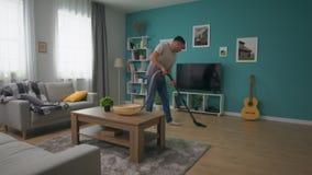 Tiro del PDA del hombre que limpia el apartamento acogedor con el aspirador almacen de video