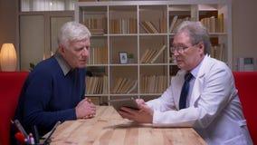 Tiro del perfil del doctor que explica a su paciente y que muestra la tableta en fondo de los estantes almacen de video