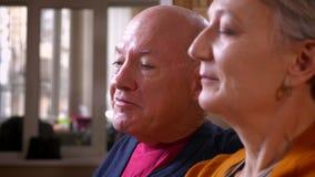 Tiro del perfil del primer de los cónyuges caucásicos mayores que hablan en videochat con sus amigos en el hogar acogedor almacen de metraje de vídeo