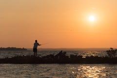 Tiro del pescador adentro al lago su cebo Fotos de archivo