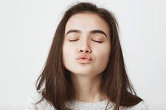 Tiro del primer del beso que espera de la mujer europea blanda atractiva para con los labios doblados y los ojos cerrados La much Imagenes de archivo