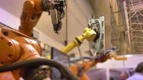 Tiro del primer de dos brazos robóticos automáticos de mudanza en proceso en fondo de la exposición almacen de video