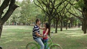 Tiro del primer de HD del movimiento adentro en pares en las bicis que charlan al aire libre almacen de video