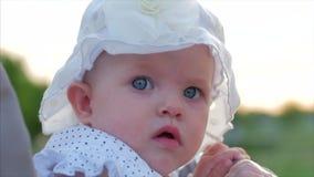 Tiro del primer de la c?mara lenta de cinco meses de beb? que se sienta al aire libre en un cochecito que mira la c?mara Mirada d almacen de video