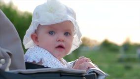 Tiro del primer de la c?mara lenta de cinco meses de beb? que se sienta al aire libre en un cochecito que mira la c?mara Mirada d almacen de metraje de vídeo
