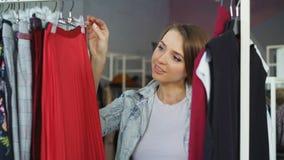 Tiro del primer de la mujer joven encantadora que elige la ropa en tienda Ella está mirando los tops, los puentes y las faldas de almacen de video