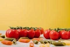tiro del primer de los tomates de cereza y de las pastas coloreadas crudas en amarillo fotos de archivo libres de regalías