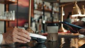 Tiro del primer del hombre irreconocible que usa actividades bancarias del pago del nfc del teléfono móvil para pagar ir café en