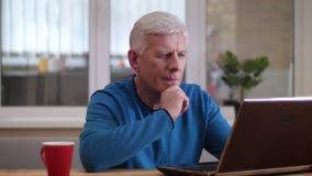 Tiro del primo piano dell'uomo caucasico invecchiato che scrive sul computer portatile all'interno in un appartamento accogliente stock footage