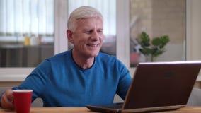 Tiro del primo piano dell'uomo caucasico invecchiato che scrive sul computer portatile che sorride felicemente all'interno in un  stock footage