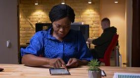 Tiro del primo piano della donna di affari afroamericana adulta che manda un sms sulla compressa nell'ufficio all'interno sul pos